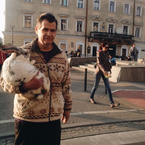 άνδρας ποζάρει έξω από ένα κτήριο κρατώντας στην αγκαλιά του έναν τεράστιο λαγό