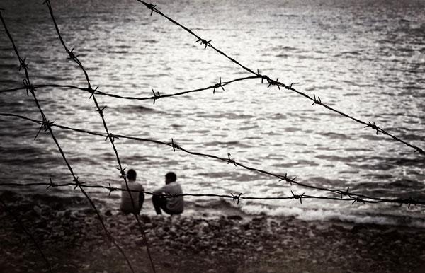πρόσφυγες καθισμένοι στην παραλία κοιτάνε το πέλαγος, συρματοπλεγματα πίσω τους
