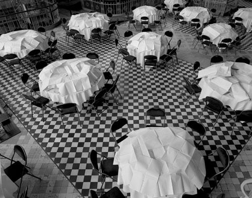 ασπρόμαυρη φωτογραφία, τραπέζια σε σχήμα ροτόντα σκεπασμένα με λευκά τραπεζομάντηλα, μάυρες καρέκλες