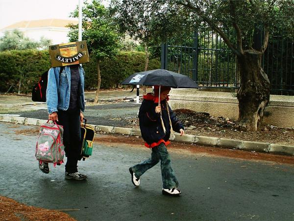 άντρας περπατάει στη βροχή κρατώντας δύο σχολικές τσάνες και με ενα χαρτοκούτι στο κεφάλι / παιδί περπατάει στη βροχή κρατώντας ομπρέλα