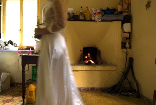 γυναικεία φιγούρα με μακρύ άσπρο φόρεμα κινείται μπροστά από τζάκι παραδοσιακού σπιτιού