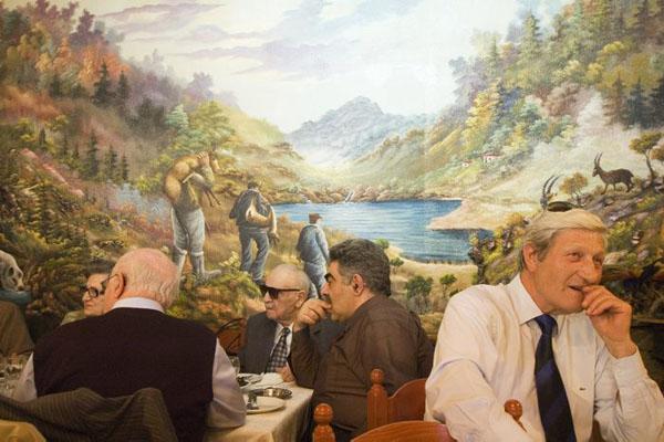 ηλικιωμένοι κύριοι και κυρίες γευματίζουν, ταπετσαρία στον τοίχο