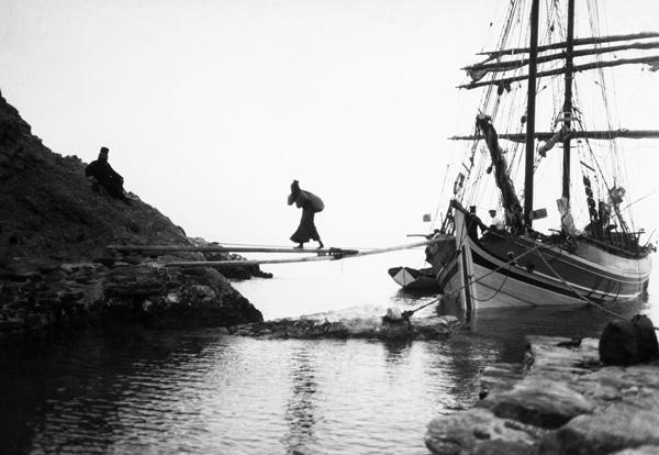 ασπρόμαυρη φωτογραφία, μοναχός κουβαλάει στις πλάτες του ένα φορτίο καραβιού περνώντας το απέναντι στη στεριά