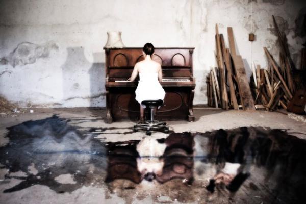 γυναίκα παίζει πιάνο σε έναν εγκαταλελλημενο χώρο