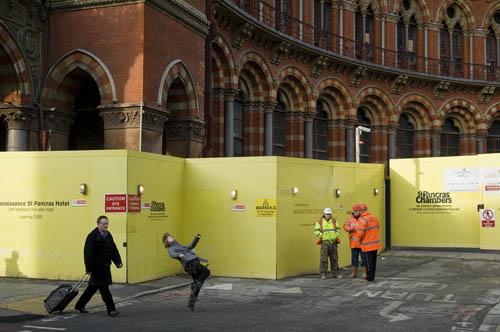 εξωτερικός χώρος κτιρίου, δημόσια έργα, εργάτες, ένα παιδί που παίζει μπάλα και ένας κύριος με βαλίτσα