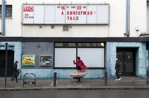 γυναίκα χορεύει έξω από ένα κατάστημα, περαστικοί