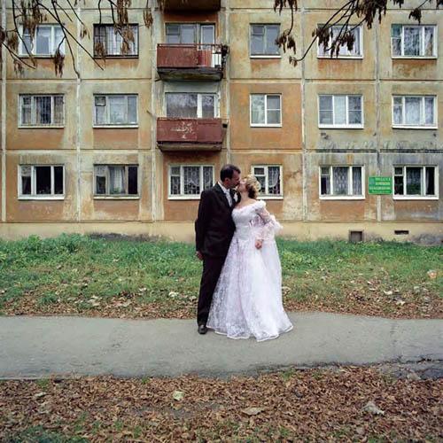 νεόνυμφο ζευγάρι, γαμήλια αναμνηστική φωτογραφία μπροστά από εργατικές κατοικίες