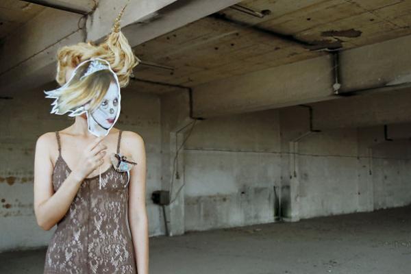 γυναίκα κρατάει στο πρόσωπό της μία μάσκα γυναίκας