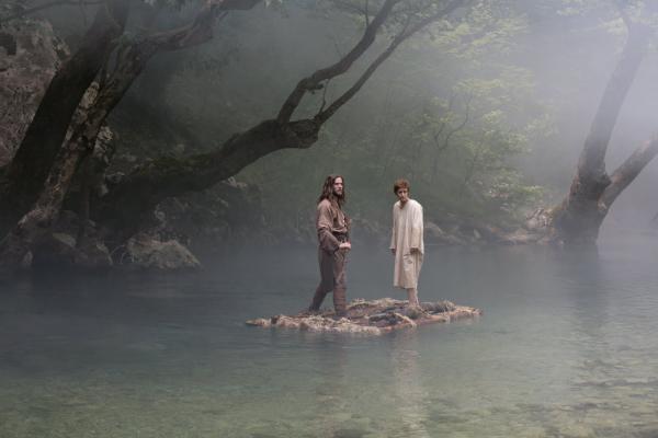 δύο άνδρες πάνω σε ένα κούτσουρο μέσα σε μια λίμνη
