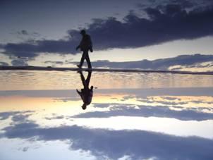 άνδρας περπατάει σε παραλία, αντανάκλαση φωτός και νερού