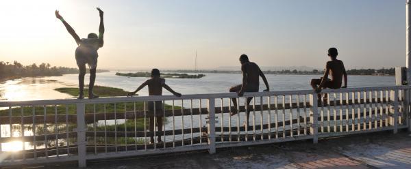 4 παιδιά κάθονται σρα κάγκελα μιας γέφυρας