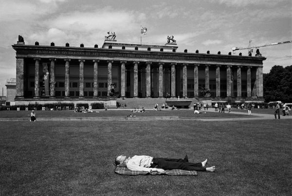 άντρας ξαπλωμένος μπροστά στο γρασίδι κτηρίου του Βερολίνου