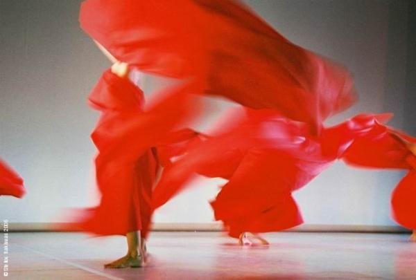 χορευτές με κόκκινο ύφασμα εν κινήσει