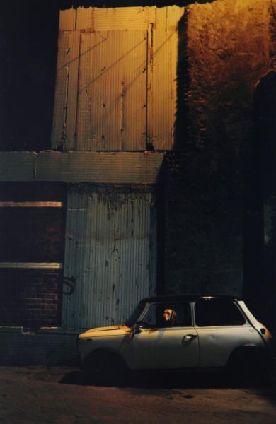 παλιό αυτοκίνητο με έναν σκύλο στη θέση του οδηγού παρκαρισμένο μπροστά απο ένα εγκαταλελλειμένο κτήριο