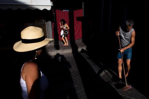 φωτογραφία δρόμου, άνδρας σκουπίζει, μια γυναίκα με καπέλο, μία περαστική γυναικα στο βάθος