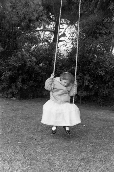 κορίτσι με μακρύ άσπρο φόρεμα κάνει κούνια