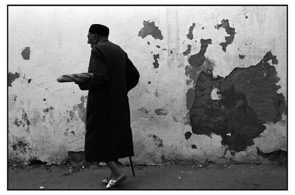 ηλικιωμένος άντρας με μάυρο παλτό και παντόφλες κρατάει ένα καρβέλι ψωμί