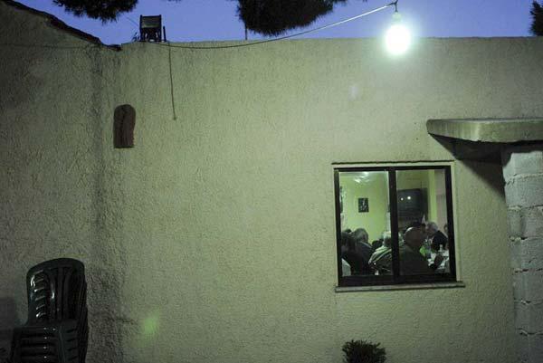 φωτογραφία έξω απο καφενείο / μέσα απο το παράθυρο φαίνονται διάφοροι άνδρες