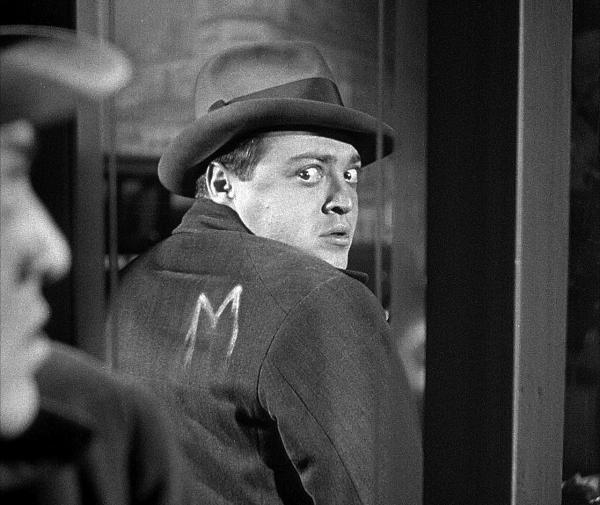 άνδρας απο την ταινία «Μ» κοιτά πίσω του φοβισμένος, φοράει καπέλο και κοστούμι και στην πλάτη του είναι σημειωμένο το γράμμα «Μ»
