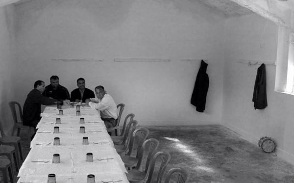 φωτογραφία: Βασίλης Αρτίκος / άνδρες κάθονται σε ένα μακρύ τραπέζι σε εσωτερικό χώρο