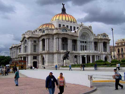 κόσμος περπατάει σε μια πλατεία μπροστα από ένα κτήριο στο Μεξικό