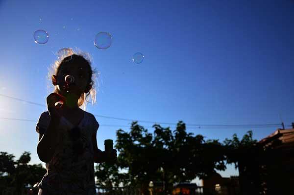 κορίτσι κάνει φούσκες με ένα ραβδί και έχει φόντο έναν καταγάλανο ουρανό