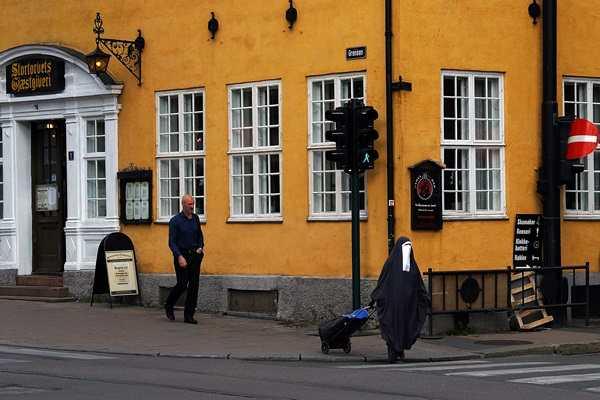 φωτογραφία δρόμου με μια καλόγρια και έναν περαστικό να περπατάνε στο πεζοδρόμιο μιας πόλης