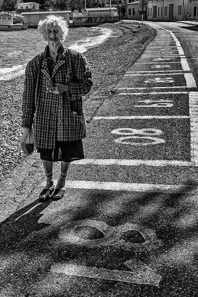 ασπρόμαυρη φωτογραφία, ηλικιωμένη γυναίκα, δρόμος με αριθμημένα κουτάκια, 80
