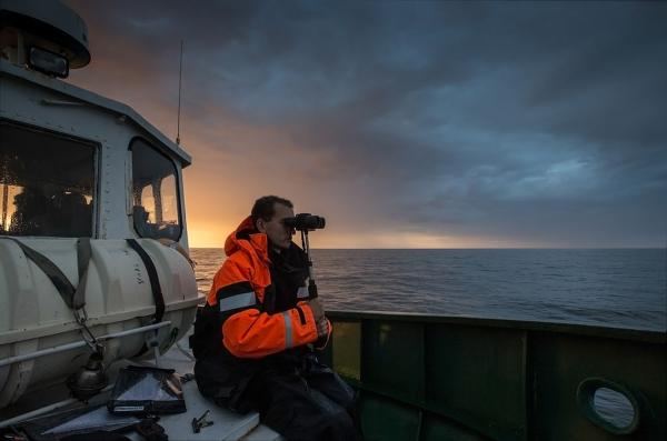 άνδρας πάνω σε καράβι στη θάλασσα κοιτά μέσα απο κυάλια
