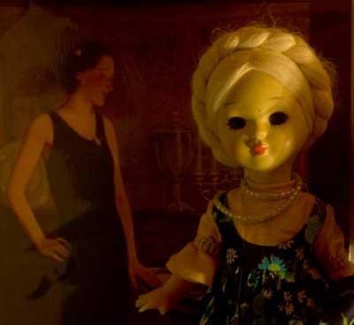μία κούκλα και στο βάθος αριστερά μία γυναίκα