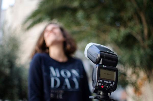 κοπέλα χαμογελά μπροστά απο μία φωτογραφική μηχανή