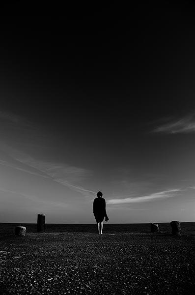 γυναίκα σκεπασμένη με μαύρο σάλο στην άκρη της θάλασσας