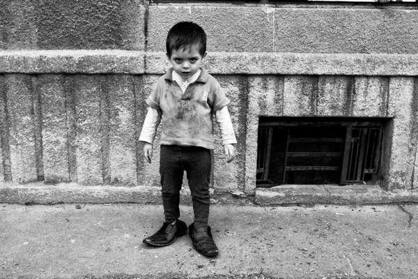 αγοράκι με λερωμένα ρούχα φοράει τα παπούτσια ενός μεγάλου