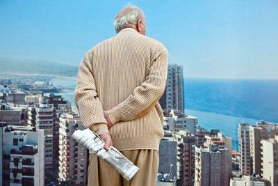 ηλικιωμένος άνδρας με γυρισμένη την πλάτη κρατάει μία εφημερίδα