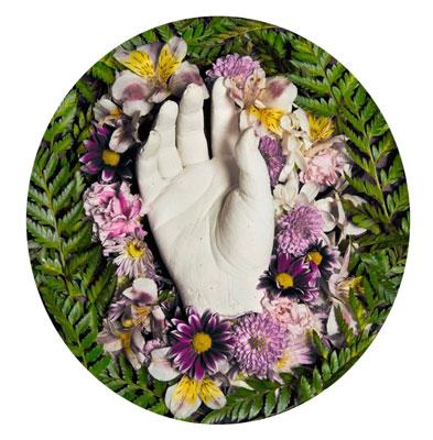 γύψινο ομοίωμα χεριού περιστοιχισμένο με λουλούδια