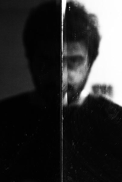 ασπρόμαυρη φωτογραφία με το πρόσωπο ενός άνδρα, διακρίνεται η μία πλερά του προσώπου