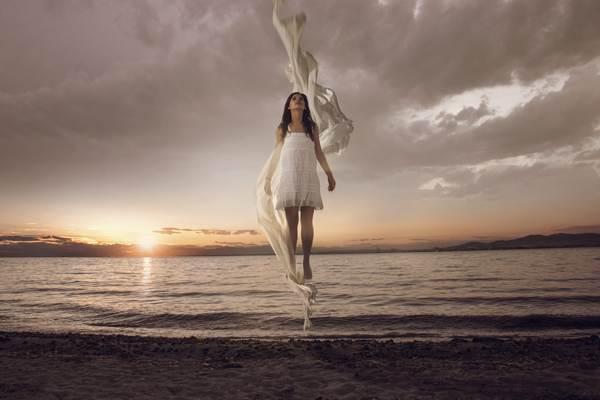 κορίτσι με λευκό φόρεμα ίπταται πάνω από τη θάλασσα την ώρα που δύει ο ήλιος