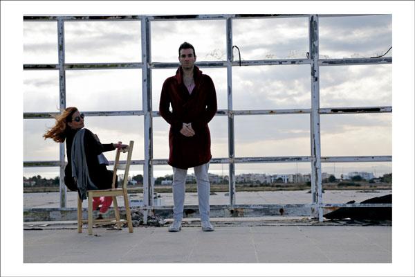 γυναίκα καθισμένη σε καρέκλα, δίπλα της άντρας όρθιος σε εγκαταλελειμένο χώρο
