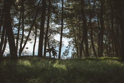 κοριτσάκι τρέχει στο δάσος κρατώντας ένα λούτρινο αρκουδάκι