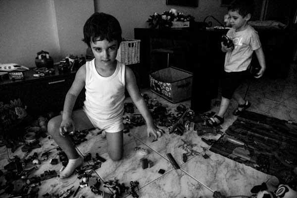 ασπρόμαυρη φωτογραφία δύο μικρών αγοριών που παίζουν με τα παιχνίδια τους στο σαλόνι του σπιτιού