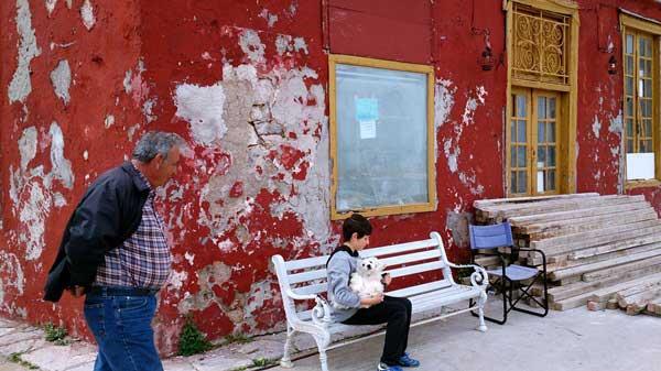 κόκκινος τοίχος / μπροστά του ένα παγκάκι στο οποίο κάθεται ένα αγόρι που κρατά ένα λευκό σκυλάκι / ένα κύριος περνά απο μπροστά τους / ΄Υδρα