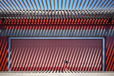 THE CHINA RED / σκιάσεις από ακτίνες ήλιου σε κόκκινο τοίχο, γυναίκα περπατάει κρατώντας ομπρέλα