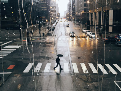 RAINY DAYS / πεζός κρατάει ομπρέλα και διασχίζει κεντρική οδό