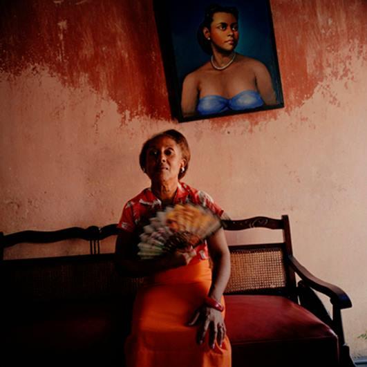Κουβανή κρατάει βεντάλια καθισμένη σε έναν καναπέ / πίσω της κρέμεται ένας πίνακας με πορτραίτο γυναίκας