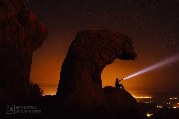 ένας άνδρας πάνω σε ένα βράχο φωτίζει με φακό τον κόκκινο ουρανό