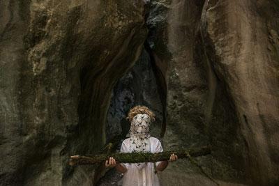 γυναίκα ποζάρει με καλυμένο πρόσωπο κρατώντας ένα κλαδί δέντρου σαν αρχαίο άγλαμα