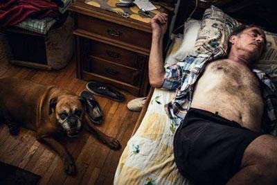 άντρας ξαπλωμένος στο κρεβάτι και ο σκύλος του στο πάτωμα