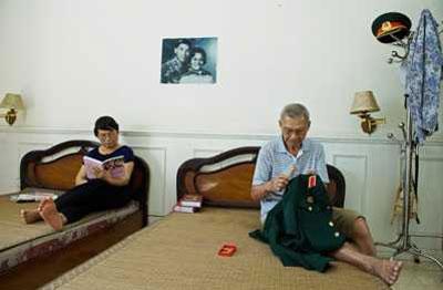 ζευγάρι βιετναμέζων καθισμένοι σε διαφορετικά κρεβάτια, ο άντρας ασχολείται με τη στολή του, η γυναίκα διαβάζει βιβλίο
