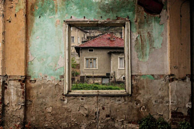 τοίχος εγκαταλελειμένου κτηρίου, από το παράθυρο φαινεται ενα σπίτι