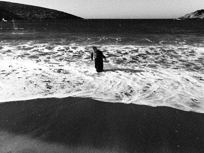 γυναίκα με μακριά μαλλιά ντυμένη στα μαύρα βγαίνει από τη θάλασσα, ασπρόμαυρη φωτογραφία
